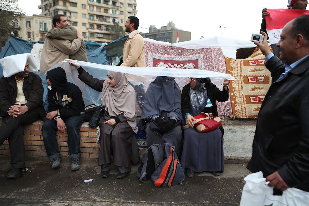 "On ""Sunday of the martyrs"" at Tahrir Square, Egyptian women take cover from the rain."