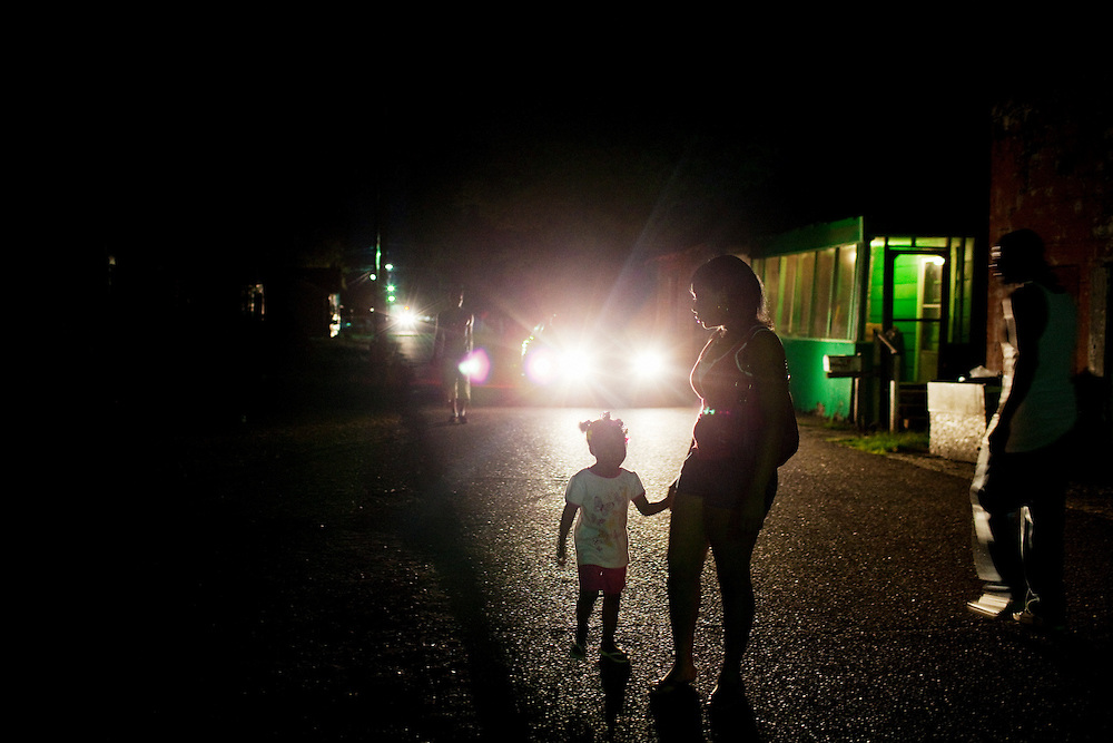 Mee Mee Williams walks at night with her daughter Cameariyana, 3, in the Baptist Town neighborhood of Greenwood, Mississippi on September 25, 2011.