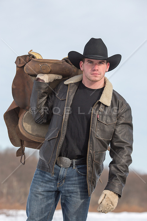 cowboy holding a saddle outdoors
