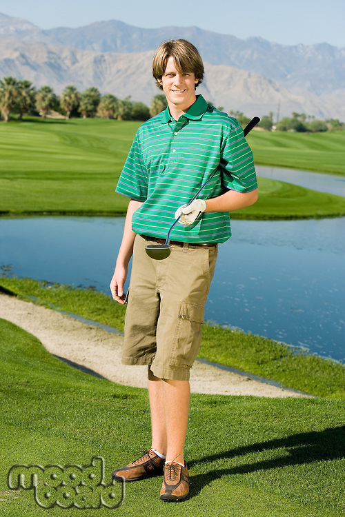 Golfer Standing on Fairway Near Water Hazard
