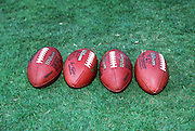 NFL footballs lie on the grass before the NFL preseason football game between the St. Louis Rams and the San Diego Chargers on Aug. 25, 2001 in San Diego. The Chargers won the game 13-10 in overtime. (©Paul Anthony Spinelli)