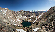 A tarn lake sits at the base of Glen Pass in the high Sierra. Glen Pass sits at 11,926 feet above sea level and offers incredible unobstructed views over the Sierra crest and the Rae Lakes Basin.