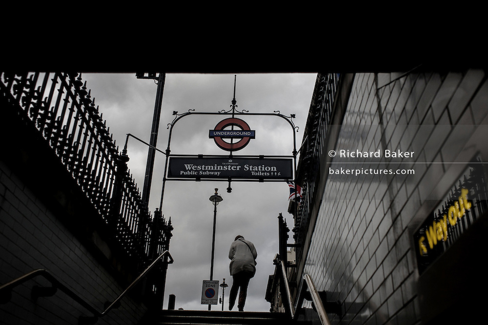 Desaturated image of commuter exits Westminster Underground station on Whitehall with the Way Out sign and arrow.