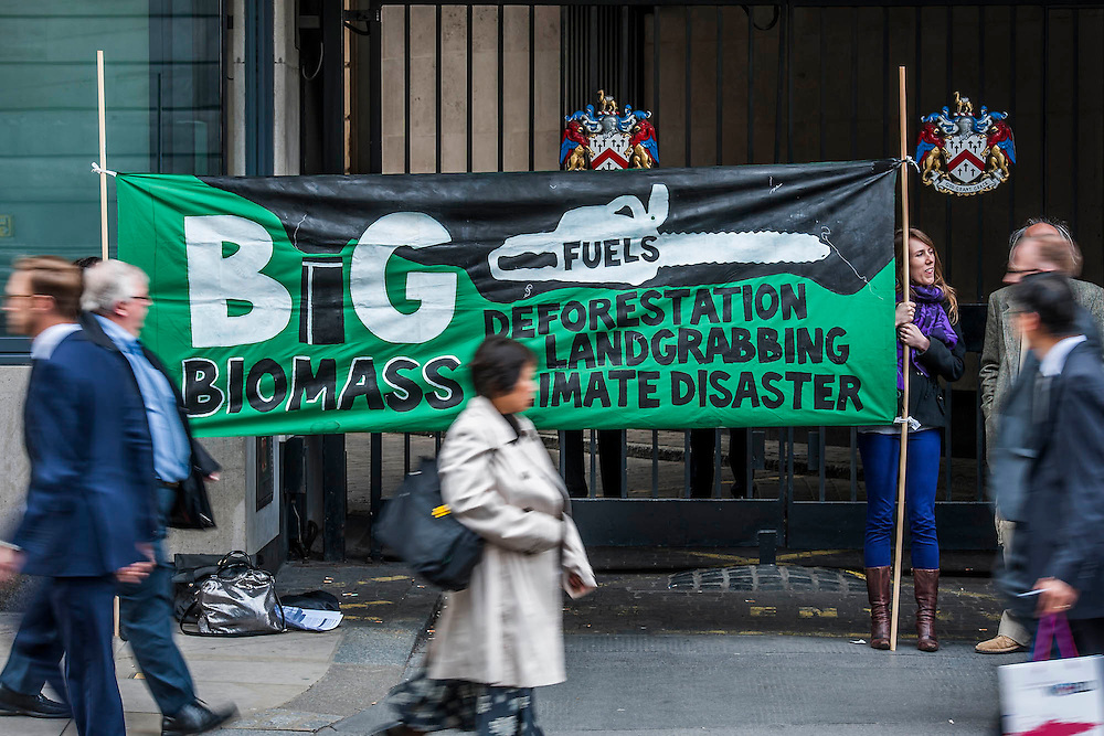 Environmental protestors lobby Drax shareholders as they arrive for its Annual General Meeting. They then picket the exit in an attempt to encourage investors to sell their shares because of risk added to the price as a result of  reliance on subsidies. Grocers hall, Bank, London, UK 23 April 2014.