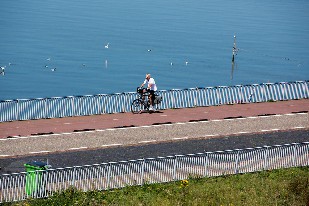 Fietsers rijden over de Afsluitdijk. In 1932 werd de opening tussen de Waddenzee (achtergrond) en de toenmalige Zuiderzee gesloten. Nu is het een belangrijke verkeersader tussen Friesland en Noord-Holland en scheidt het de Waddenzee met het IJsselmeer.<br /> <br /> Cyclists are riding on the Afsluitdijk. In 1932, the gap between the Wadden Sea and the former Zuiderzee closed by the Afsluitdijk. Now it is a major thoroughfare between Friesland and North Holland and it separates the Wadden Sea from the IJsselmeer.