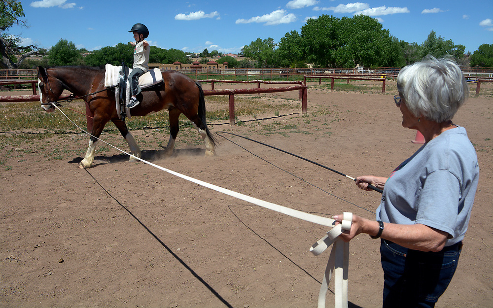 gbs050717w/LIVING -- Sue Corlew of Albuquerque leads Kirby Jack, a Clydesdale and quarter horse cross, as Matthew Fehr, 9, of Albuquerque, practices vaulting moves during practice at the Cloud Dancers of the Southwest Therapeutic Horsemanship Program. (Greg Sorber/Albuquerque Journal)