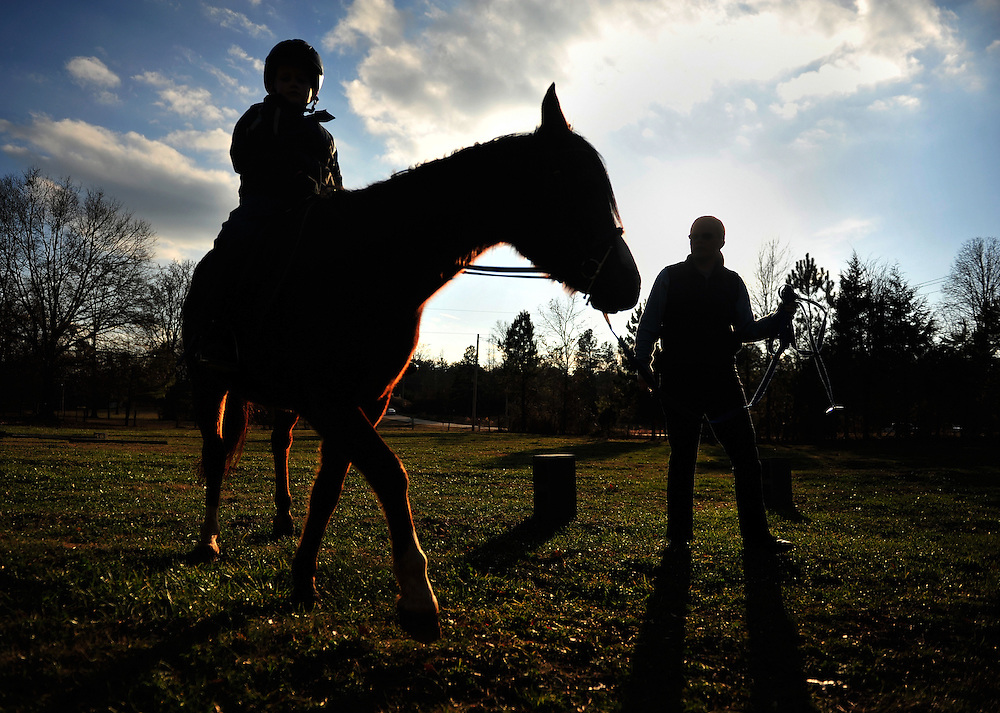 Laura DePooter walks along with Hunter Swafford, 8, as he rides Mage during a therapeutic riding session at DePooter's Madison County farm on Thursday, Jan. 6, 2010 in Madison County, Ga.  Swafford is developmentally challenged and is currently being tested for autism.