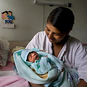 Placida Canchari Meza, 38, and mother of six, holds her hours old newborn at the Ayacucho regional Hospital. ..The Ayacucho Regional Hospital is the largest government hospital in the region - serving approximately 580,000 people. The hospital is committed to respecting the practices of the indigenous community within the region by supporting their traditional birthing practices. Doing so encourages more indigenous women to give birth in the hospital while maintaining their cultural practices, but in a safer environment thereby reducing maternal mortality. Vertical birthing, for example, is common for the Qechua community. Women believe that their feet should be planted on the ground when they are giving birth and their partners need to be involved in the process by typically standing behind them and pushing on the women's belly while she delivers the baby.