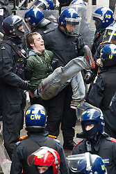 © Licensed to London News Pictures . 11/06/2013 . London , UK . A man kicks up as he's lead away by police  from inside after police cut their way in with an angle grinder . Police surround a former police station on 40 Beak Street , Soho this morning (11th June) . The site has been occupied by organisers of today's Stop G8 anti capitalist protests . Demonstrations in London today (Tuesday 11th June 2013) ahead of Britain hosting the 39th G8 summit on 17th/18th June at the Lough Erne Resort , County Fermanagh , Northern Ireland , next week . Photo credit : Joel Goodman/LNP