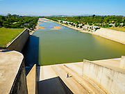 01 JULY 2015 - NONG BUA, LOPBURI, THAILAND: A maintenance worker walks across a spillway at Pa Sak Dam. Normally there's water in the spillway. Central Thailand is contending with drought. By one estimate, about 80 percent of Thailand's agricultural land is in drought like conditions and farmers have been told to stop planting new acreage of rice, the area's principal cash crop. Water in reservoirs are below 10 percent of their capacity, a record low. Water in some reservoirs is so low, water no longer flows through the slipways and instead has to be pumped out of the reservoir into irrigation canals. Farmers who have planted their rice crops are pumping water out of the irrigation canals in effort to save their crops. Homes have collapsed in some communities on the Chao Phraya River, the main water source for central Thailand, because water levels are so low the now exposed embankment is collapsing. This is normally the start of the rainy season, but so far there hasn't been any significant rain.     PHOTO BY JACK KURTZ