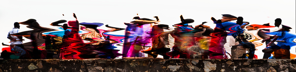 An abstract interpretation of a brightly dressed musical troupe singing and dancing along the old Portuguese ramparts.<br /> (Photo by Matt Considine - Images of Asia Collection)