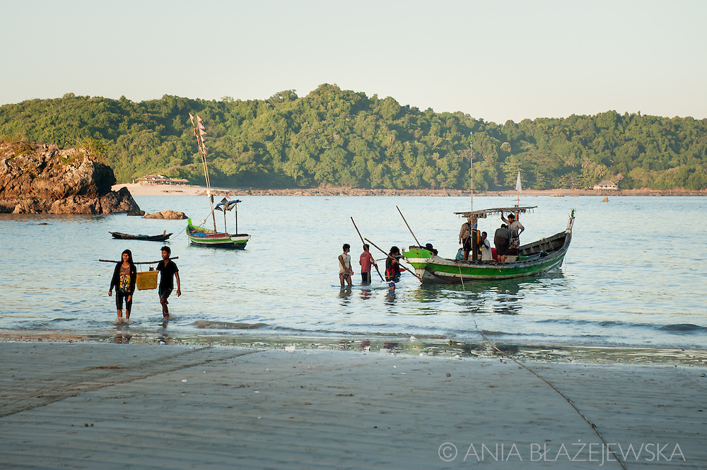 Myanmar, Ngapali. Men come back with their catch early in the the morning.<br /> Every single morning all the fisherman from the little village at Ngapali Beach come back home with their night catch. At the beach all the women wait for them and afterwards work with drying and selling fish and other creatures from the sea begins.