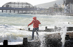 © Licensed to London News Pictures. 10/10/2014<br /> A man playing with the waves.<br /> Eastbourne Seafront today (10.10.2014) <br /> A windy sunny day on Eastbourne seafront in East Sussex.<br /> (Byline:Grant Falvey/LNP)
