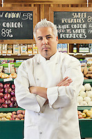 Portrait of a confident chef with arms crossed in market