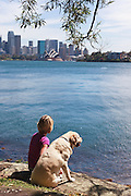 Woman with dog looking from Cremorne Point to Opera House, Sydney, Australia
