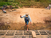 11 MARCH 2016 - LUANG PRABANG, LAOS: A crewman jumps on a ferry across the Mekong River near Luang Prabang. Laos is one of the poorest countries in Southeast Asia. Tourism and hydroelectric dams along the rivers that run through the country are driving the legal economy.       PHOTO BY JACK KURTZ