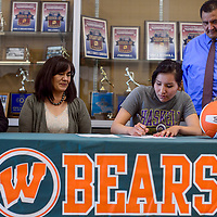 Keziah Pine, center, sits with her parents Mary Pine, right, and Donald Pine and her coaches Melody West, left, and Karen Malone as she signs her letter of intent to play volleyball for Haskell Indian Nations University Monday at Wingate High School.