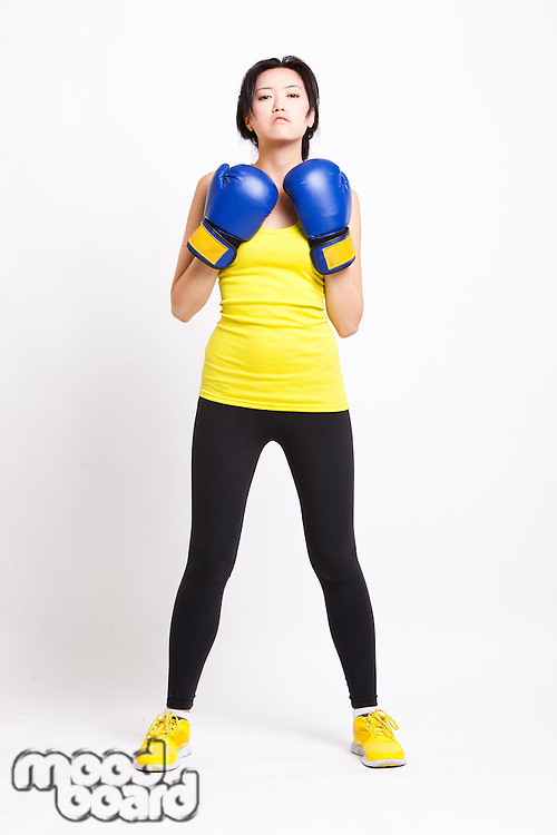 Portrait of confident Asian woman wearing boxing gloves against white background