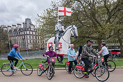 © Licensed to London News Pictures. 22/04/2015. Wellington Arch, London. Tourists on Boris bikes meet the 15ft St George unveiled by English Heritage at Wellington Arch, in honour of the Patron Saint, ahead of England's largest St George's Day celebration at Wrest Park as well as the launch of a nationwide tour which will see the knight open jousting tournaments at castles across England. Photo credit : Stephen Chung/LNP