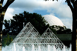 Disney World's water sculptures provide a foreground for the world renowned Friendship Earth ball in the background.  The monorail track is just behind the 2 pyramids. Note: This image was originally produced on film and scanned to produce a digital file.  Some dust may be visible from that scan