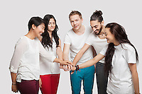Side view of young multi-ethnic friends in casuals over white background