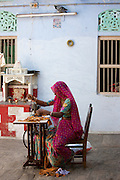 Indian woman wearing traditional Rajasthani sari works at home using sewing machine in village of Nimaj, Rajasthan, Northern India