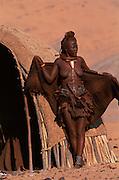Himba woman beside traditional house. Kaokoland, Namibia.
