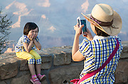 Mother and daughter dressed alike at Grand Canyon overlook; daughter poses for camera phone