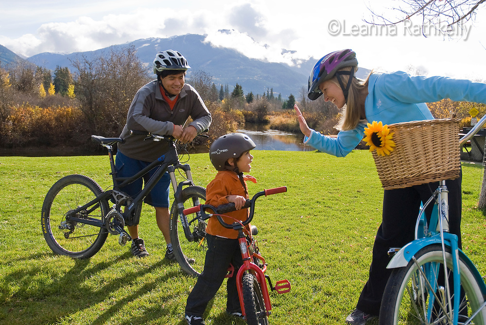 A family bikes along the trail near Meadow Park Recreation Centre, along the River of Golden Dreams. Whistler Mountain rises in the background.