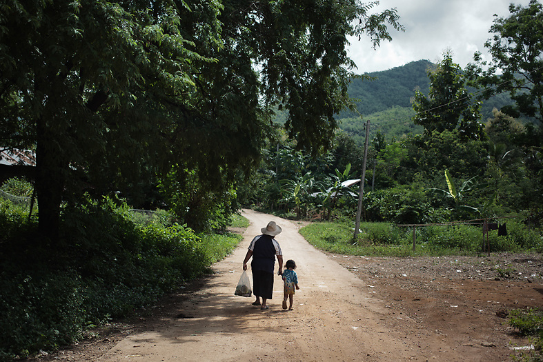 Mother and daughter walk through Samphu village on their way back to Pak Ok, where the first case of surrogacy was recorded.<br /> Lom Sak, Petchabun province, Thailand. Aug 25 2014<br /> Credit : Giorgio Taraschi for The New York Times