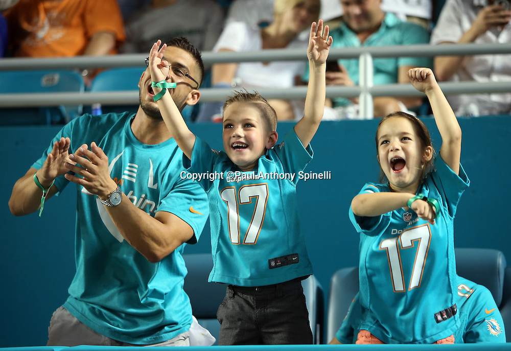Three Miami Dolphins fans cheer wildly during the NFL week 14 regular season football game against the New York Giants on Monday, Dec. 14, 2015 in Miami Gardens, Fla. The Giants won the game 31-24. (©Paul Anthony Spinelli)