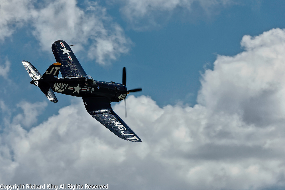 Photographic image of a World War II F-4U Corsair of the U. S. Navy performing aerobatics.