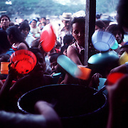 Displaced by civil war, families line up for food in a camp run by the Catholic Church in  San Salvador 1981.