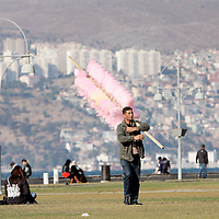 A man walks through a green space selling cotton candy in Izmir, Turkey.