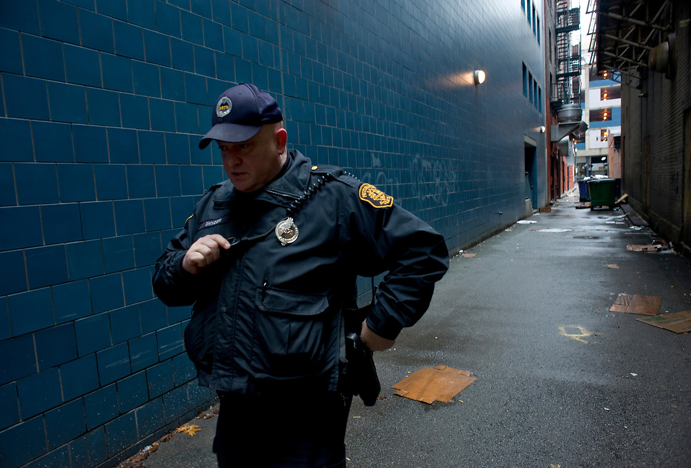 Pittsburgh Police Officer James Snyder takes a call while patrolling McCrea Way behind the O'Reilly Theater.