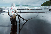 30 JULY 2013 - KOH SAMET, RAYONG, THAILAND: Workers wrestle with an oil soaked absorption boom on Ao Prao beach on Koh Samet island. About 50,000 liters of crude oil poured out of a pipeline in the Gulf of Thailand over the weekend authorities said. The oil made landfall on the white sand beaches of Ao Prao, on Koh Samet, a popular tourists destination in Rayong province about 2.5 hours southeast of Bangkok. Workers from PTT Global, owner of the pipeline, and up to 500 Thai military personnel are cleaning up the beaches. Tourists staying near the spill, which fouled Ao Prao beach, were evacuated to hotels on the east side of the island, which was not impacted by the spill. PTT Global Chemical Pcl is part of state-controlled PTT Pcl, Thailand's biggest energy firm.       PHOTO BY JACK KURTZ