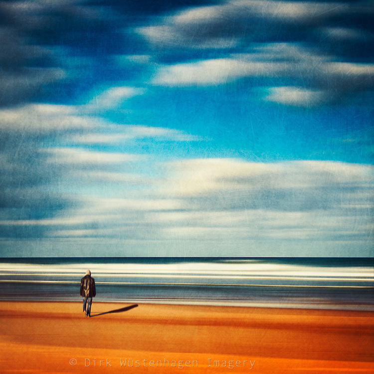 Man walking towards the ocean - abstraction of a beach scene.