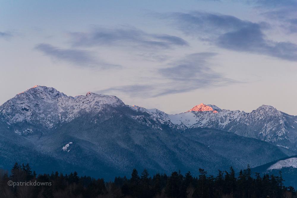 Sunrise skims the new snow on the peak, Olympic Range.