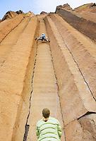 Women rock climbing on basalt columns in central Oregon USA.