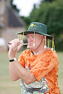 Photo by Andrew Tobin/Tobinators Ltd - 07710 761829 - representing Australia, Bruce Pattern shoots his laser sighted pea shooter during the World Peashooting Championships held at Witcham, Cambridgeshire, UK on 13th July 2013. Run in conjunction with the village fair, the Championships have been held in Witcham since 1971 when they were started by a Mr Tyson, the village schoolmaster, in order to raise funds for the village hall.Competitors come from as far afield as the USA and New Zealand to attempt to win the event. The latest technology is often used, including laser sights and titanium and carbon fibre peashooters. All peashooters must conform to strict length rules, not exceeding 12 inches, and have to hit a target 12 feet away. Shooting 5 peas at a plasticine target attached to a hay bale, the highest scorers move through the initial rounds to a knockout competition, followed by a sudden death 10-pea shootout.