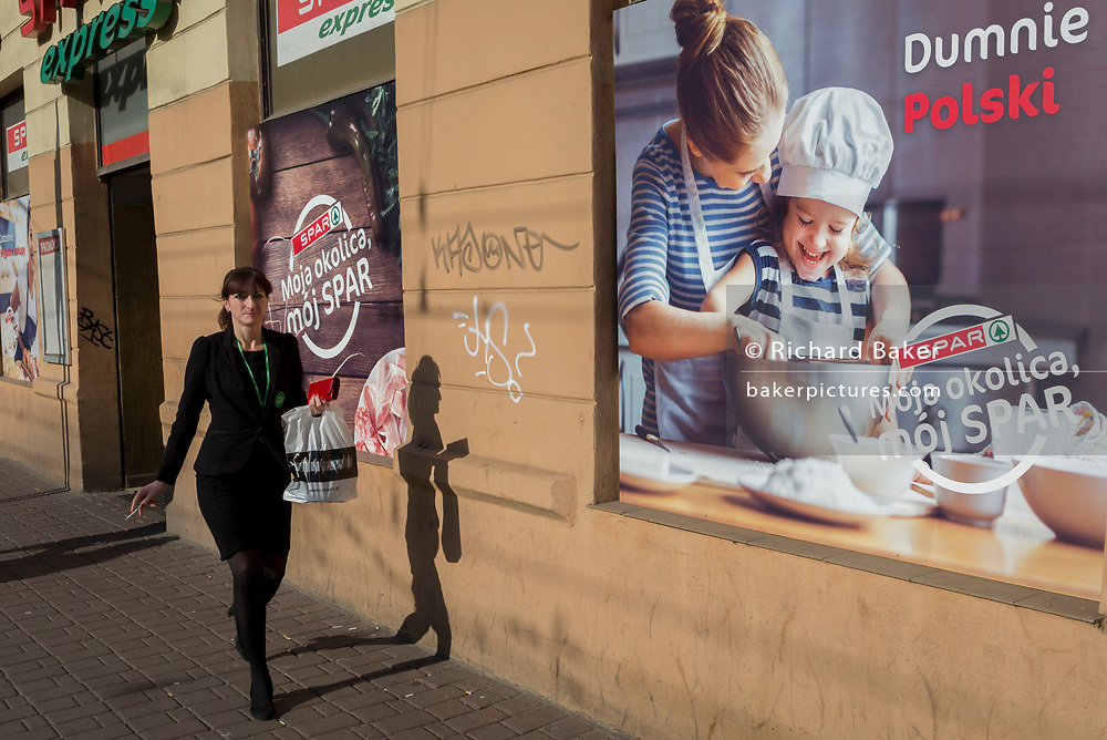 A young modern Polish women walks and smokes a cigarette, passing a poster outside a Spar supermarket that shows the stereotyping of gender: a mother and her daughter enjoying baking in the kitchen together, on 23rd September 2019, in Krakow, Malopolska, Poland. The poster translates as: 'My neighborhood ,my spar'.