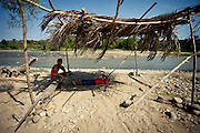 Marco Ruiz Reyes relaxes in the shade with a friend at the hottest hour of the day. Many men from the village work on digging out stones on the river bank which are later used in construction.
