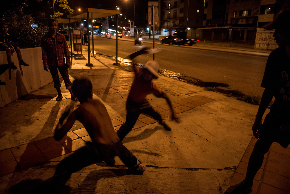 """CARACAS, VENEZUELA - OCTOBER 17, 2017:  Young members of a street gang of homeless boys practice sparring with sticks and crushed water bottles - to become more agile at knife fights with rival street gangs. The gang leader requires them to practice every day for at least 30 minutes. They spar two at a time, until one is able to touch the other with their fake knifes. Once that happens, they are considered """"stabbed and hurt"""", and lose the round. The gang leader says the rule is everyone for themselves. If anyone in the gang is attacked by a single member of a rival gang, no matter how young they are - they must defend themselves alone, even to the death.  The only time other members of the gang step in is when one of their members is being attacked by multiple members of a rival gang. Four young members of their gang have been stabbed to death in recent moths. Those who have been in the streets for more than a few moths all have scars they say are from knife fights.  A growing number of young boys  are leaving their homes outside of the city to live in the streets of Caracas where it is easier for them to attain food. They join street gangs with other homeless youth, and engage in knife fights in order to expand and defend their territories and control over sought after areas for panhandling and picking through garbage. Several young gang members interviewed by The New York Times said they prefer to live in the streets, despite the danger - because they eat better than they could living at home with their families. PHOTO: Meridith Kohut for The New York Times"""