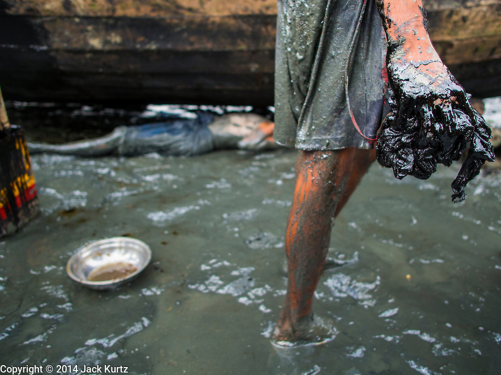 07 NOVEMBER 2014 - SITTWE, RAKHINE, MYANMAR: A worker's hands, covered in tar, near a boat he is working on in the port of an IDP camp for Rohingya Muslims near Sittwe. The government of Myanmar has forced more than 140,000 Rohingya Muslims who used to live in Sittwe, Myanmar, into squalid Internal Displaced Person (IDP) camps. The forced relocation took place in 2012 after sectarian violence devastated Rohingya communities in Sittwe and left hundreds dead. None of the camps have electricity and some have been denied access to regular rations for nine months. Conditions for the Rohingya in the camps have fueled an exodus of Rohingya refugees to Malaysia and Thailand. Tens of thousands have put to sea in rickety boats hoping to land in Malaysia but sometimes landing in Thailand. The exodus has fueled the boat building boom on the waterfront near the camps. Authorities expect the pace of refugees fleeing Myanmar to accelerate during the cool season, December through February, when there are fewer storms in the Andaman Sea and Bay of Bengal.   PHOTO BY JACK KURTZ