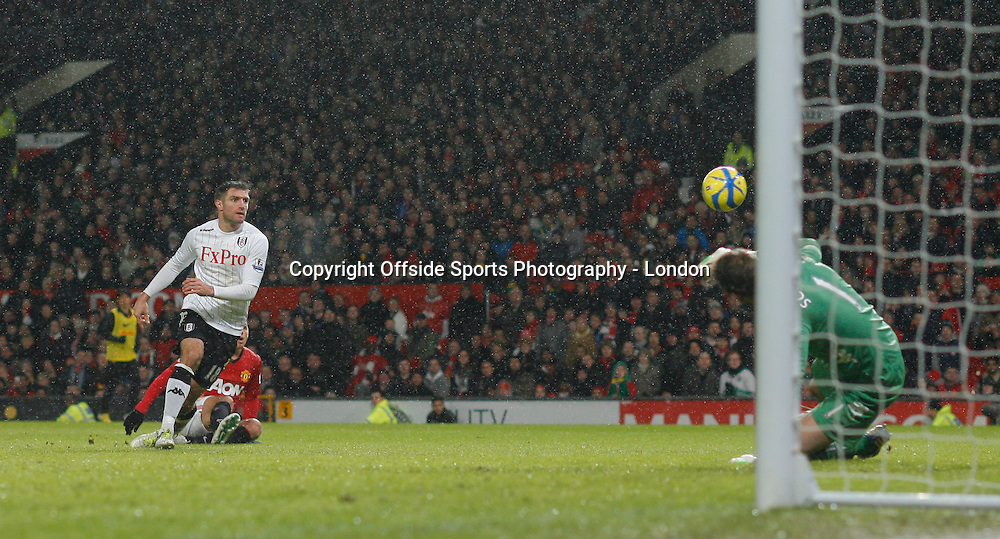 26 January 2013 FA Cup Manchester United v Fulham.<br /> Javier Hernandez shoots and the ball deflects off Aaron Hughes and past Mark Schwarzer for the fourth United Goal.<br /> Photo: Mark Leech.