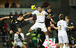 SWANSEA, WALES - Saturday, December 8, 2012: Swansea City's captain Ashley Williams in action against Norwich City's captain Grant Holt during the Premiership match at the Liberty Stadium. (Pic by David Rawcliffe/Propaganda)