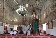 Muslims praying in the Et'hem Bey Mosque or Xhamia e Et'hem Beut, begun 1789 by Molla Bey and finished in 1823 by his son Haxhi Ethem Bey, great-grandson of Sulejman Pasha, Tirana, Albania. The frescoes decorating the mosque, unusual in Islamic art, depict swirling vegetal patterns. The mihrab indicates the direction of Mecca and the wooden minbar or pulpit is on the right. The mosque is listed as a Cultural Monument of Albania. Tirana was founded by the Ottomans in 1614 by Sulejman Bargjini and became the capital of Albania in 1920. Picture by Manuel Cohen