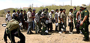 A group of illegal immigrants from Mexico waits deportation by U. S. Border Patrol agents in Sells, Arizona on the Tohono O'odham Nation.