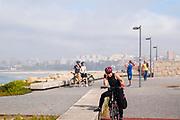 woman cycles on the Eurovelo 1 Atlantic coast route Near Vila Nova de Gaia and Porto, Portugal. The Atlantic coast on the left