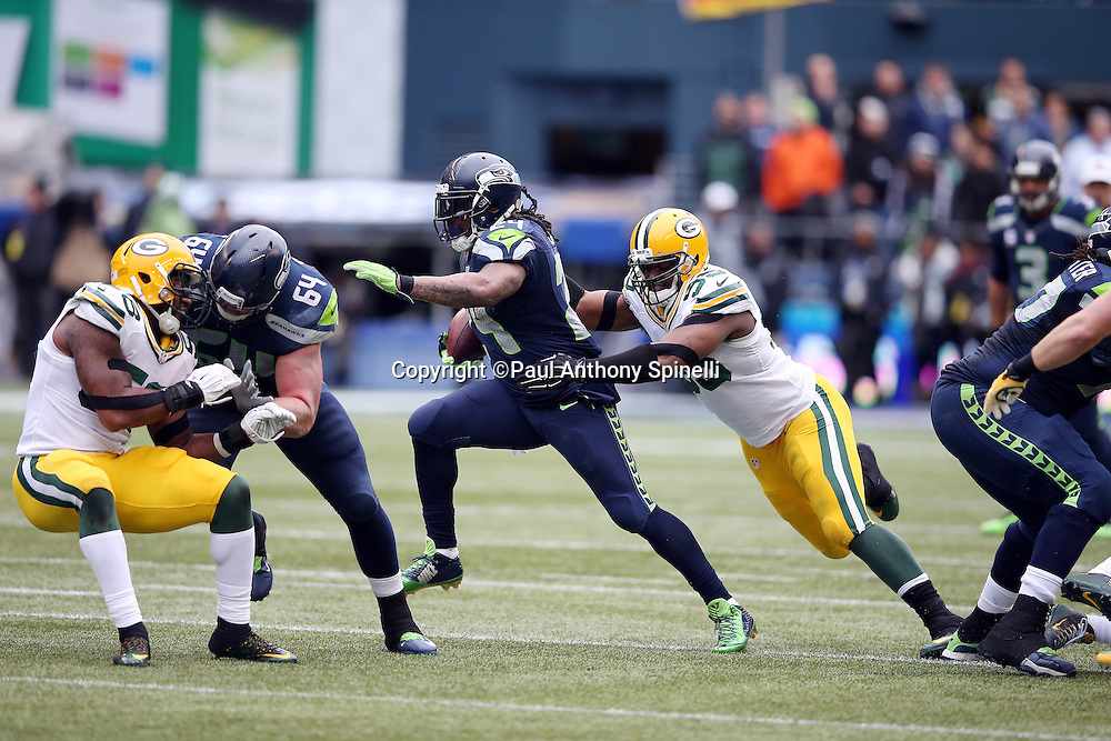 Seattle Seahawks running back Marshawn Lynch (24) high steps away from a tackle attempt by Green Bay Packers defensive end Datone Jones (95) as he runs for a gain of 10 yards on a third quarter second down play with 30 yards to go for a first down during the NFL week 20 NFC Championship football game against the Green Bay Packers on Sunday, Jan. 18, 2015 in Seattle. The Seahawks won the game 28-22 in overtime. ©Paul Anthony Spinelli
